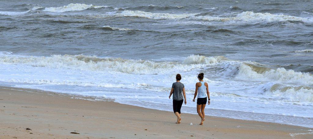 Donne che camminano in spiaggia, camminare benefici, crescita personale