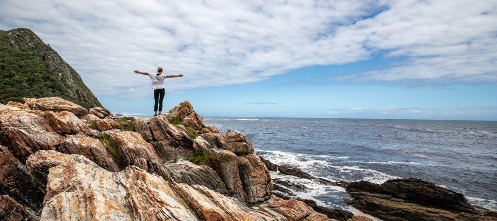 Ragazza che apre le braccia verso il mare, scegliere crescita personale